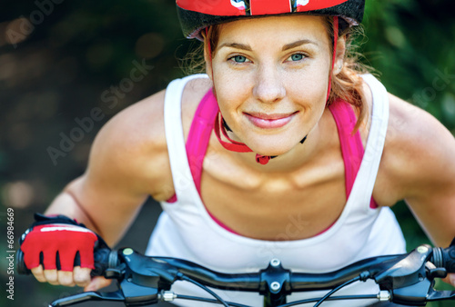 Photo Stands Cycling Happy Young woman leaned over the handlebars of her bike.