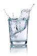 canvas print picture - Eiswürfel fällt in ein Glas mit Wasser