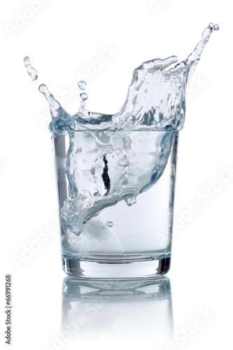 Fototapeta Eiswürfel fällt in ein Glas mit Wasser obraz