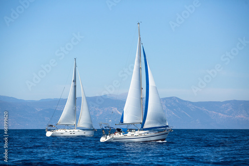 Fototapeta Group of sail yachts in regatta near a coast.