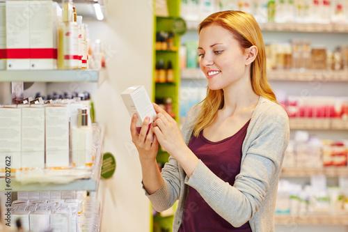 Fotografie, Obraz  Frau hält Produkt in der Drogerie in der Hand
