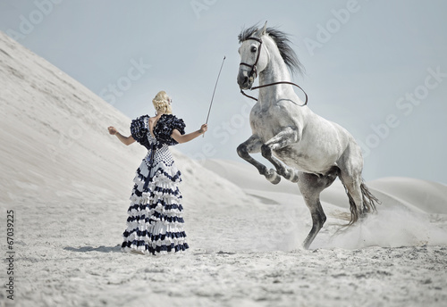 Poster Foto van de dag Attractive blonde training the horse