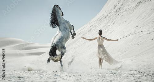 Obraz Ładna pani z ogromnym koniem na pustyni - fototapety do salonu