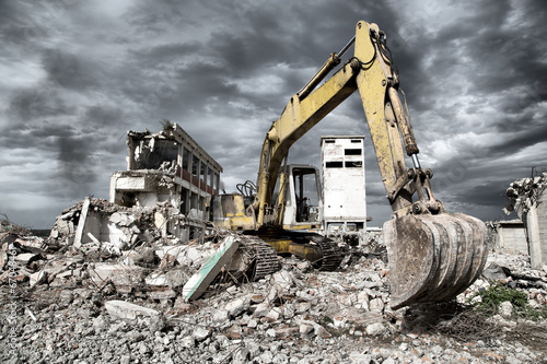 Photo  Bulldozer removes the debris from demolition of old buildings