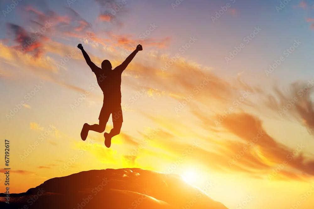 Fototapeta Happy man jumping for joy on the peak of the mountain. Success