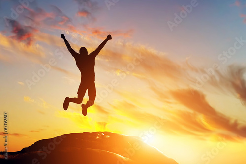 Photo  Happy man jumping for joy on the peak of the mountain. Success