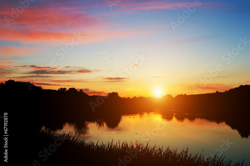 Lake in forest at sunset. Romantic sky with red clouds