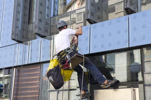 Photo Climber wash windows and glass facade of the skyscraper
