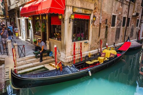 Fototapeta Tourists travel on gondolas at canal