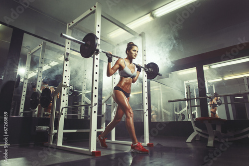 Young sexy girl in the gym doing squat on smoke background