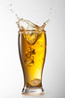 Ice falling into beer glass with splash isolated on white