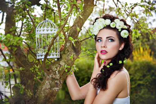 Fotografia  Woman with white flowers in hair and birdcage