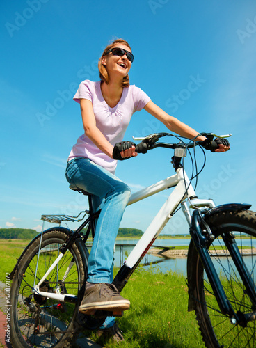 Keuken foto achterwand Ontspanning Young woman is sitting on her bicycle