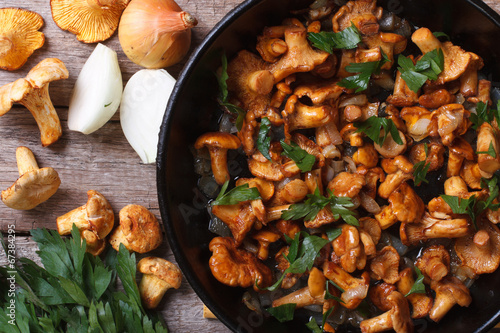 Carta da parati chanterelle mushrooms with onion and parsley  in a pan top view