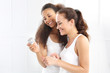 Dwie kobiety czytają napisy na słoiczku z kremem.