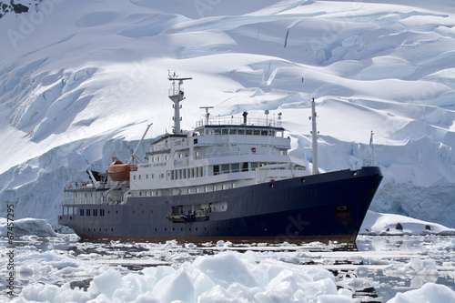 big blue tourist ship in Antarctic waters against the backdrop o