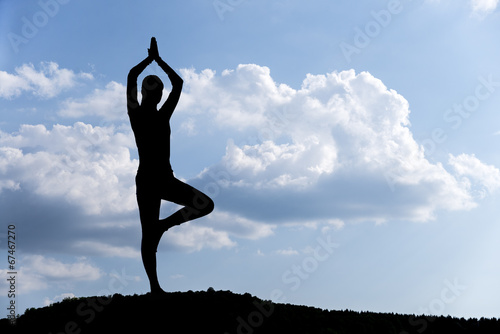 Foto  Pretty woman doing yoga exercises in the park. silhouette.