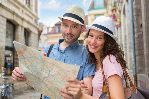 Fotografia  Couple of young attractive tourists watching map