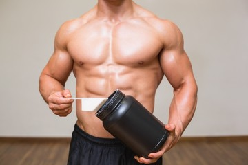 FototapetaBody builder holding a scoop of protein mix in gym
