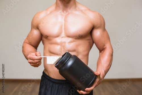 Body builder holding a scoop of protein mix in gym - 67482807