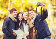 canvas print picture - group of friends with photo camera in autumn park