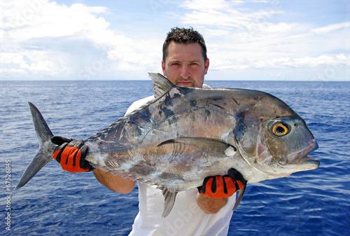 Fotografia  Pêcheur tenant une carangue prise à la ligne