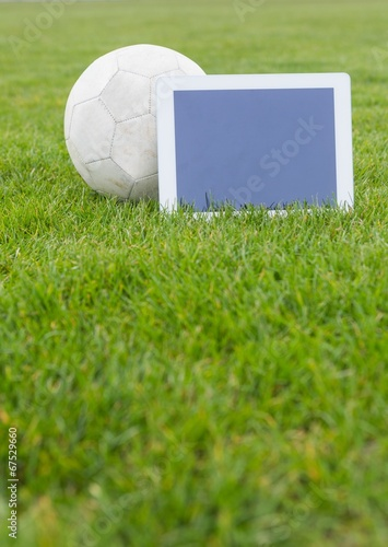 Fotografiet  Football and tablet with blank screen on pitch