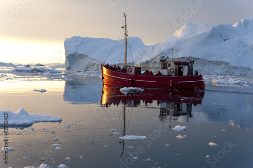 Red fishing boat around icebergs at Disko Bay, Ilulissat