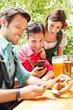 Männer im Biergarten schauen auf ihre Smartphones