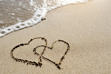 Love Concept - Two Hearts Drawn On The Beach Sand