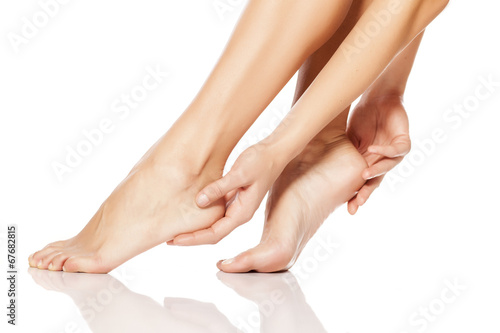 Foto op Aluminium Pedicure woman tenderly touching her feet