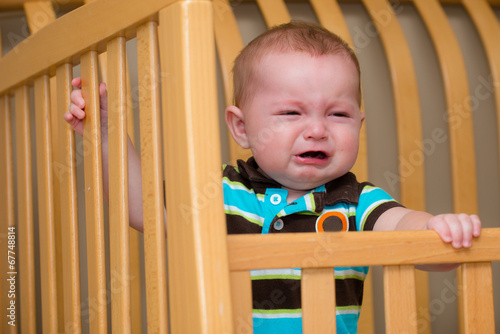 Valokuva  Crying unhappy baby standing in his crib