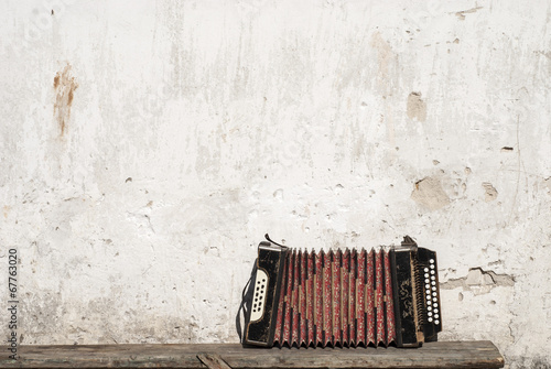 Fotografía  wall and accordion on the bench background