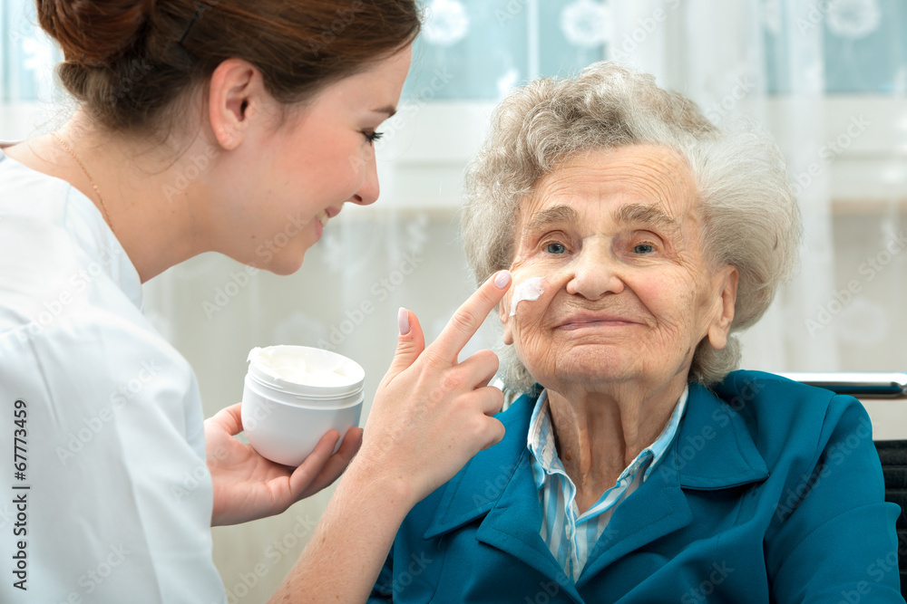 Fototapeta Elderly woman is assisted by nurse at home