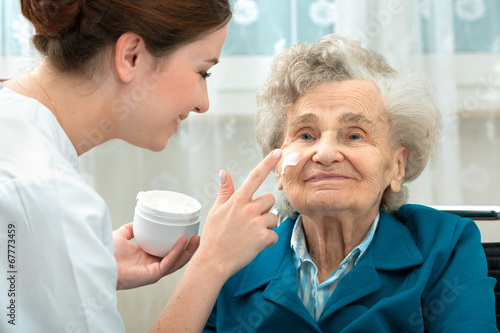 Obraz Elderly woman is assisted by nurse at home - fototapety do salonu