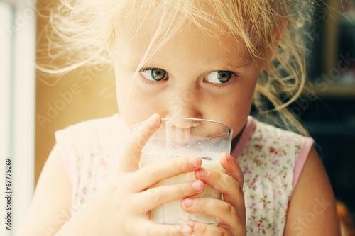 Carta da parati Cute cheerful little girl drinking milk