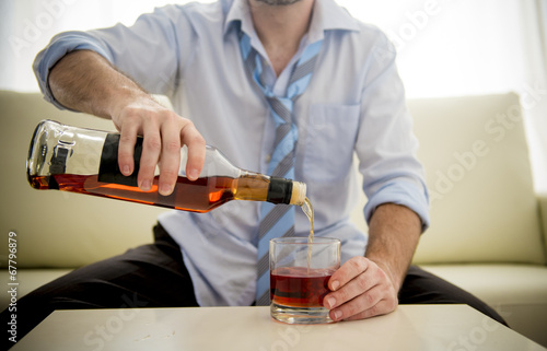 Fotografía  nk Businessman filling whiskey glass sitting on couch at home