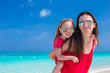 Young mother and little daughter have fun at tropical beach