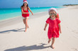Young mother and little girl have fun at tropical beach