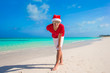Young man on tropical beach in Christmas Hat