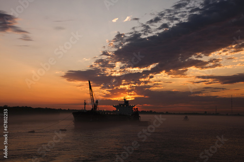 In de dag Schip Cargo ship underway at sunset
