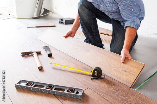 Obraz Man installing new laminated wooden floor - fototapety do salonu