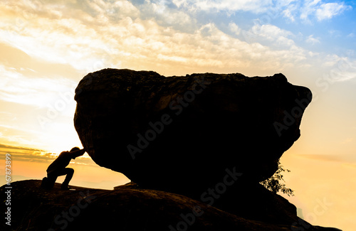 Fotografia  Hard work.The person rolls the rock on mountain.