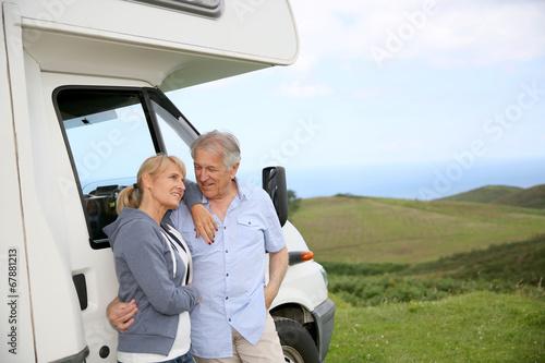 Cuadros en Lienzo Senior couple standing by motorhome in countryside