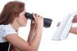 Frau mit Sehschwäche liest mit Fernglas