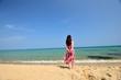 海を眺めるピンクのドレスを着た女性の後ろ姿