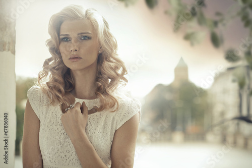 Fotografía  Blond lady with curly hairstyle posing outdoor