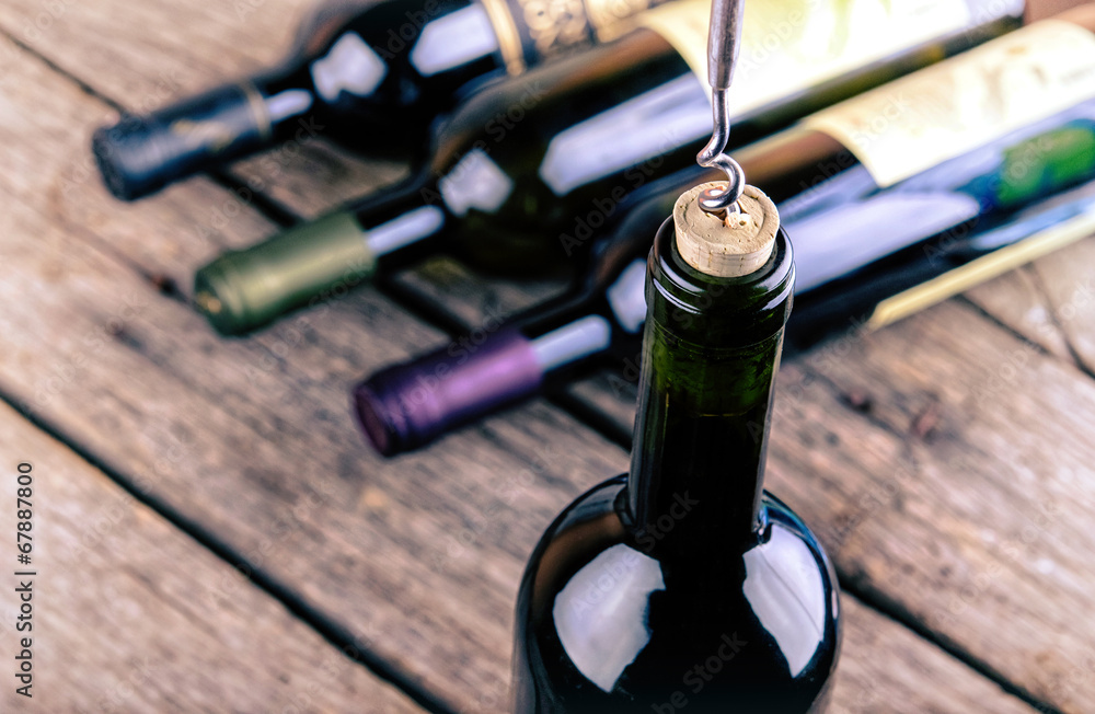 Wine bottle on a wooden table Poster