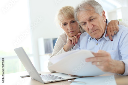 Fotografering  Senior couple doing the income tax declaration online