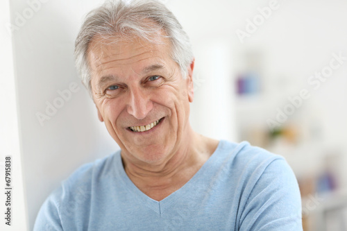 Portrait of smiling senior man with blue shirt Wallpaper Mural